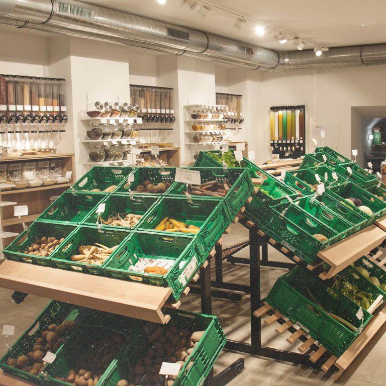 Ein Foto des Ladeninneren. In der Mitte grüne Kisten mit Obst und Gemüse. Im Hintergrund Lebensmittel-Spender zum Gefäße selbst-befüllen und die Kühlung.
