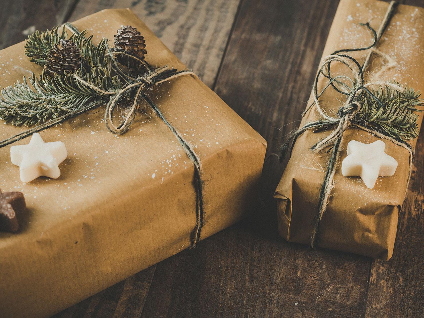 In Naturpapier verpackte Geschenke, dekoriert mit Tannenzweigen und Tannenzapfen
