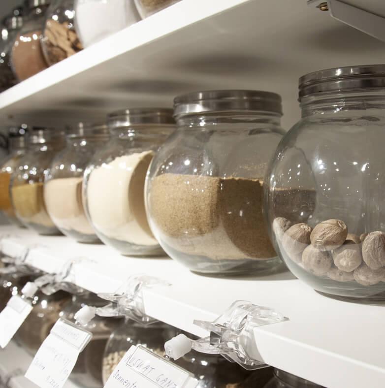 Gemahlenes und Muskatnüsse in Glasbehältern mit Schraubdeckel